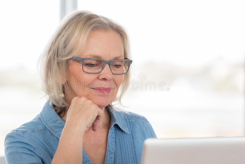 年长膝上型计算机妇女 免版税库存照片