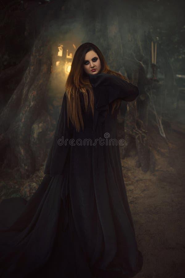 黑长袍的一个少妇有看直接地c的长的头发的 免版税库存图片