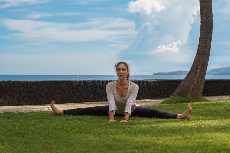 长袍的美丽的女孩在海洋海滩做瑜伽实践,凝思,舒展asana在巴厘岛印度尼西亚 免版税图库摄影