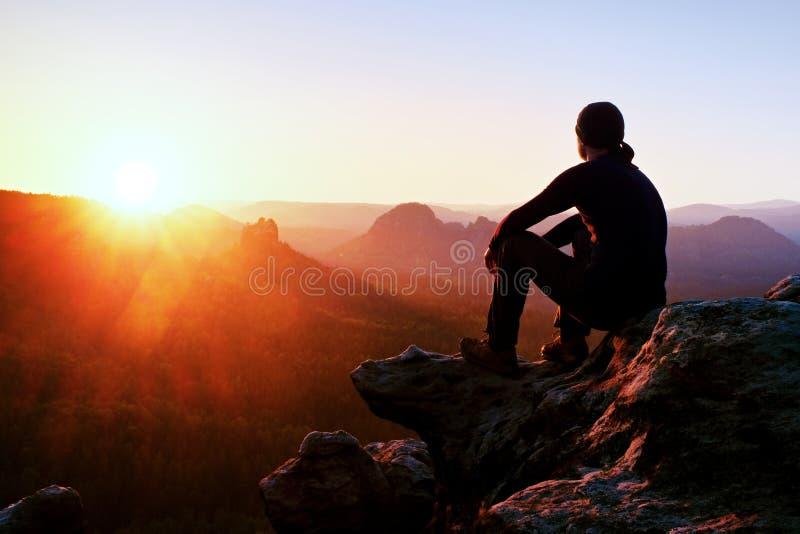 黑长裤的疲乏的成人远足者,夹克和黑暗的盖帽坐峭壁边缘和看对在谷轰鸣声的五颜六色的薄雾 免版税库存图片
