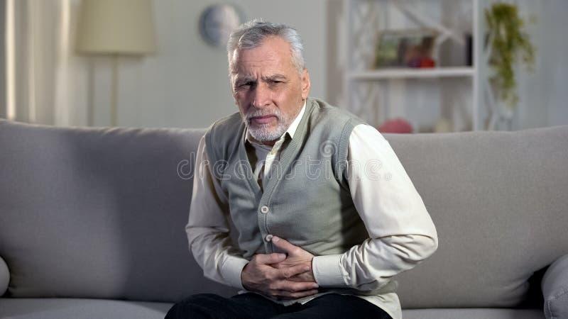 长辈男性遭受的肚子疼,在上部腹部的锋利的抽疯,消化不良 库存图片