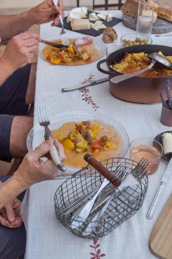 长辈的夫妇的手有吃白色桌布的晚餐一起自创食物过程 库存照片