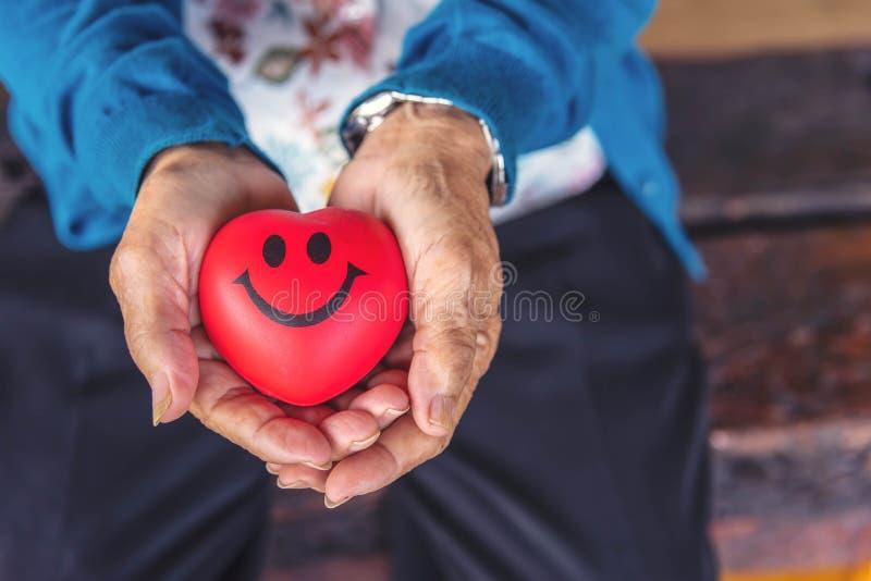长辈资深妇女藏品读了与微笑的心脏 wom的关闭 免版税库存图片