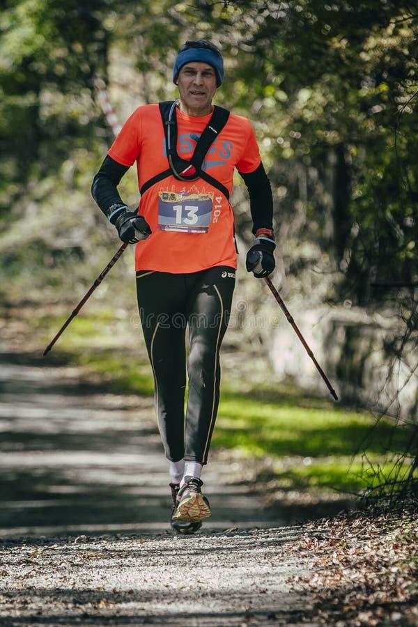 年长运动员跑用棍子到步行距离种族 免版税库存照片