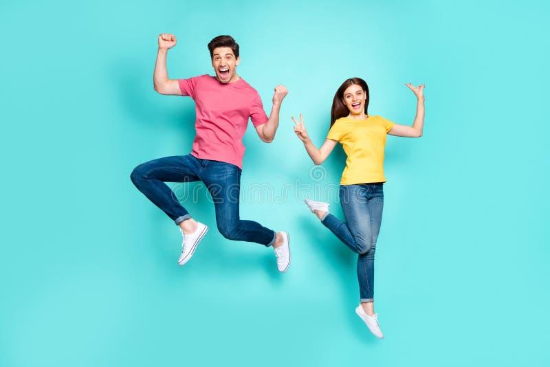 长长体型视野中的迷人、活泼、快乐的疯狂情侣在空中跳跃玩v 库存图片