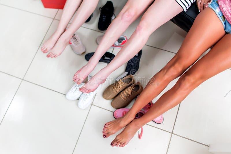 延长他们长的赤足腿的三个少妇的播种的图象放松在选择在购物的鞋子以后 库存图片