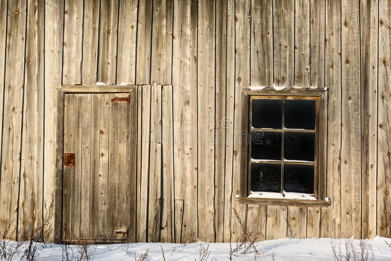 门和窗口在一个老木谷仓的墙壁上 库存图片