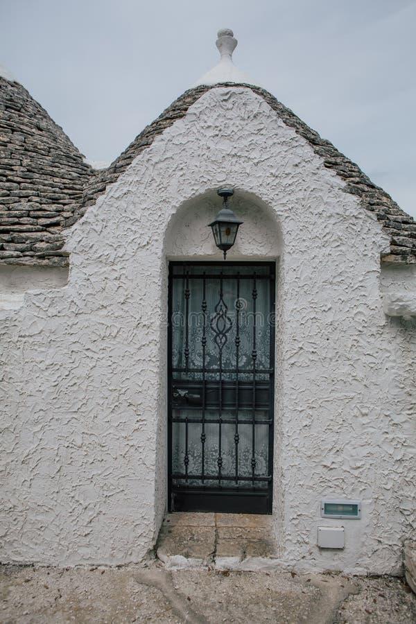 门在Trullo trulli城市街道的nd窗口在意大利 库存图片