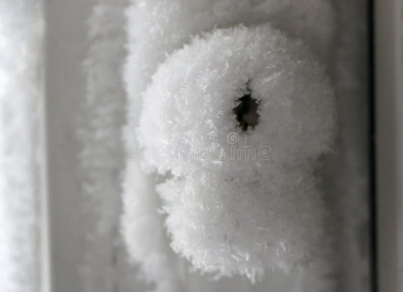 门把手和匙孔用霜严厉霜盖 门结冰 冰冷的用雪花盖的把柄和锁 免版税库存图片