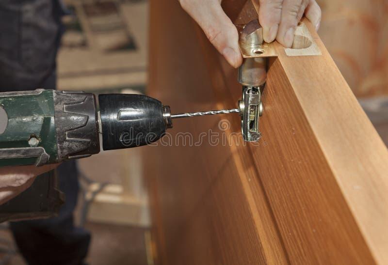 门架置,安装deadbolt锁,电钻操练的hol 库存照片