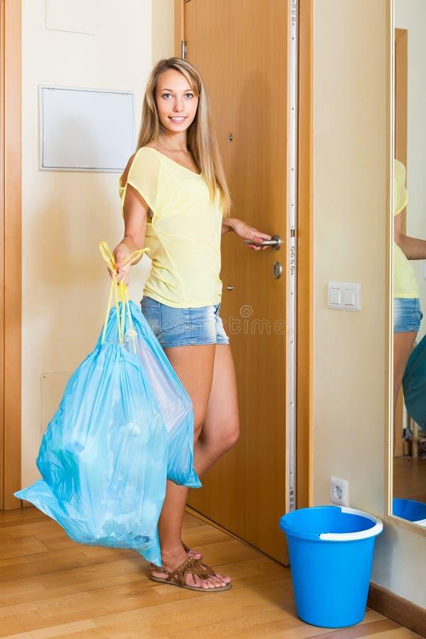门的女孩与垃圾袋 免版税库存照片
