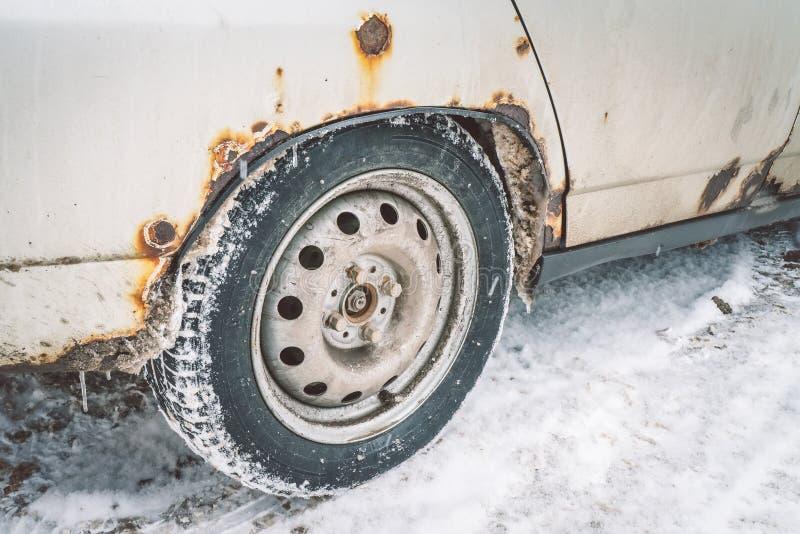 门的底部和白色汽车的底部在冬天报道以一个刻薄铁瑕疵 库存图片