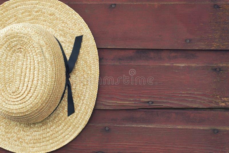门诺派中的严紧派的人的草帽在一个红色毂仓大门垂悬 免版税库存图片