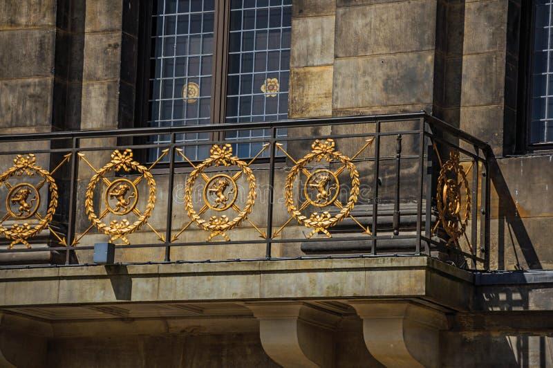 门面特写镜头与阳台的和金黄铁楼梯栏杆在阿姆斯特丹王宫  免版税图库摄影
