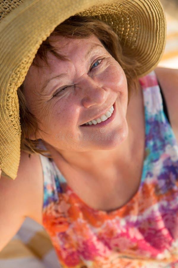 闪光与一只眼睛的微笑的资深妇女对在sunbed的海滩 图库摄影