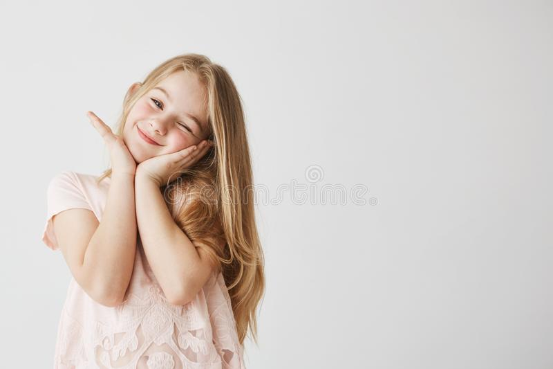 闪光美丽的矮小的白肤金发的女孩对照相机微笑,摆在,感人的面孔用她的在桃红色逗人喜爱的礼服的手 孩子 免版税库存图片