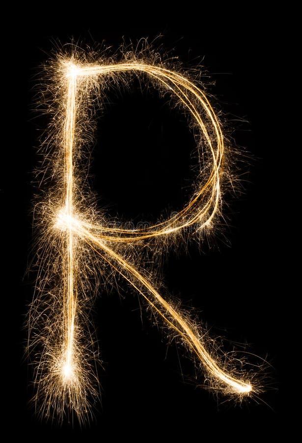 从闪烁发光物字母表的英国信件R在黑背景 库存照片