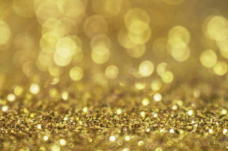 闪烁金背景 与发光金黄圈子bokeh的圣诞节纹理作为淡色的抽象样式holida的 库存图片