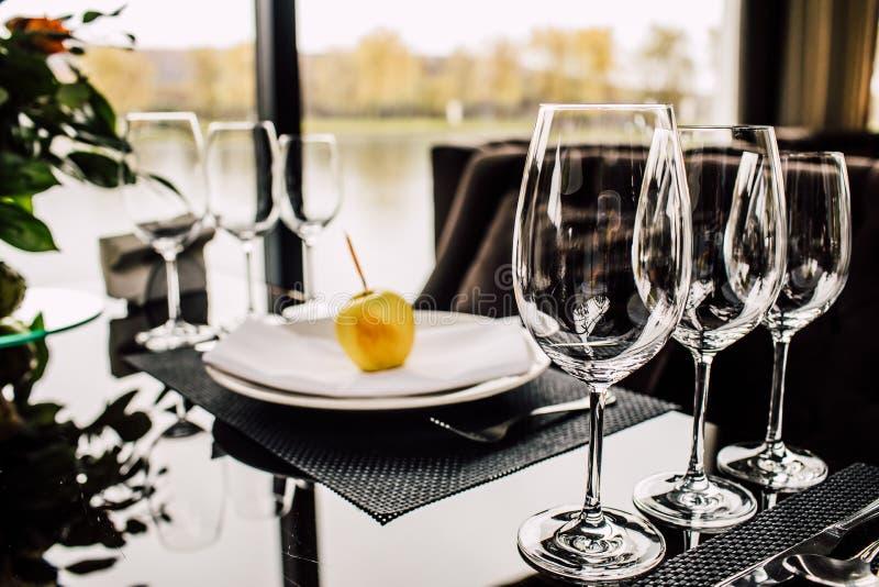 闪耀的玻璃器皿在为婚姻的二准备的长的桌上站立 库存照片
