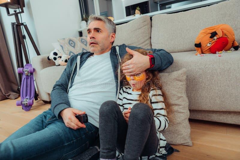 闭上他的女儿眼睛用他的手的运动服的英俊的父亲 库存照片