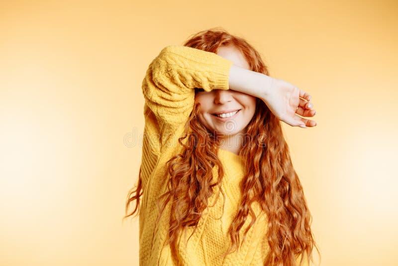 闭上她的与手逗人喜爱的微笑的佩带的明亮的毛线衣的好姜年轻女人眼睛 愉快的卷曲女孩掩藏的面孔用手  免版税库存图片