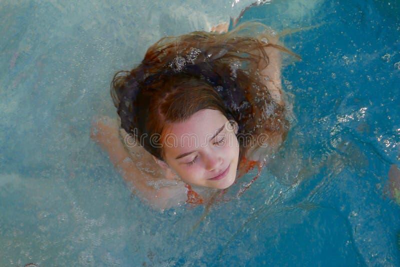 闭上她的眼睛的女孩,当放松在温泉水池时 库存图片