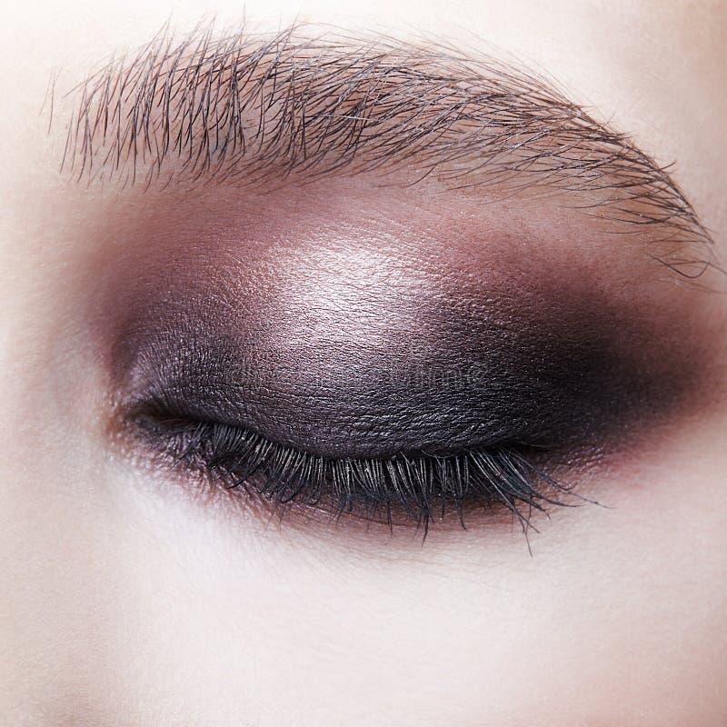 闭合的人的女性眼睛特写镜头宏观画象  有完善的紫罗兰的-黑发烟性眼睛构成女孩 免版税库存照片