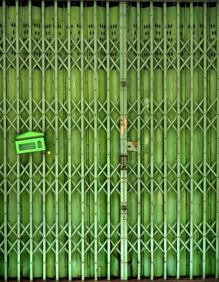 闭合的可撤回的可折叠金属门 免版税库存照片