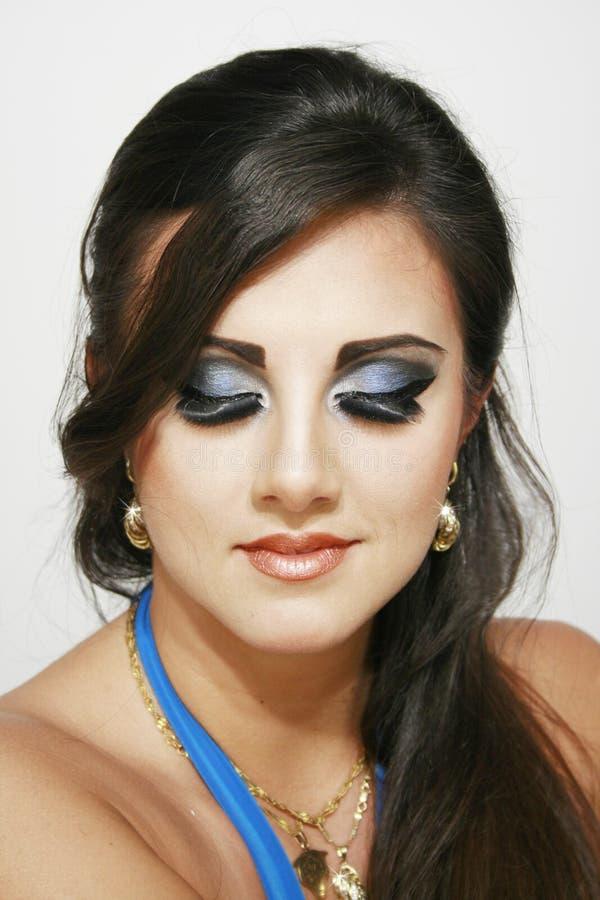 闭合的有蓝色强烈的构成和earings的眼睛美丽的女孩,与长的黑发 免版税库存图片