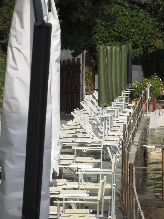 闭合的海滩睡椅和伞线准备好在下夏季 意大利托斯卡纳 免版税库存照片