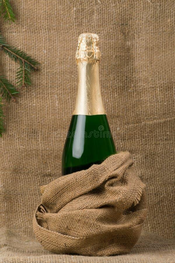 闭合的瓶香槟酒,反对粗糙,棕色织品背景  免版税库存图片