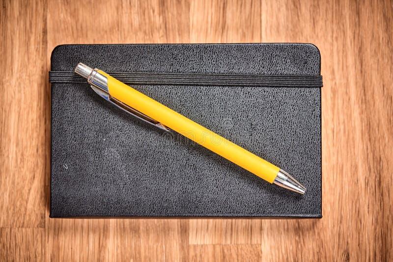闭合的笔记本和圆珠笔在一张棕色木桌上 免版税库存图片