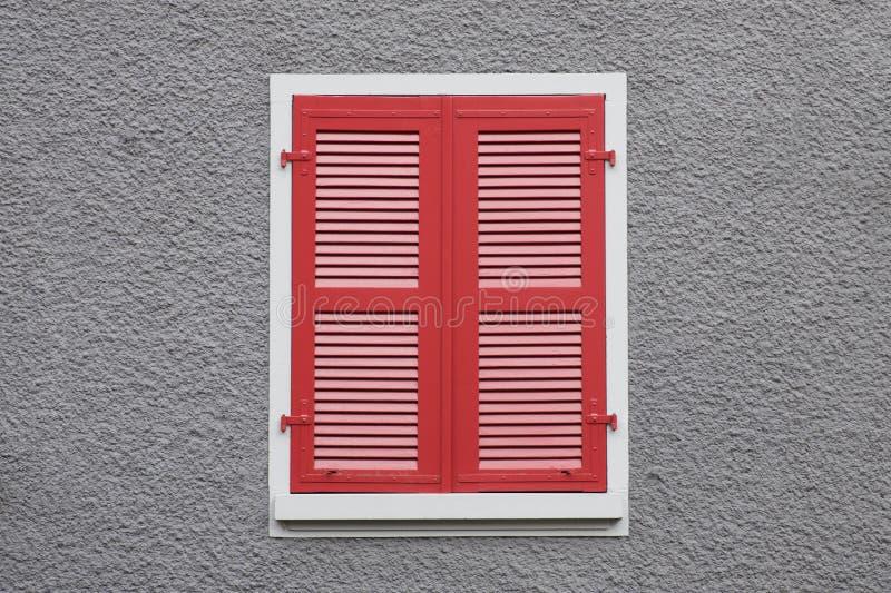 闭合的红色木窗口快门对灰色墙壁 免版税库存图片