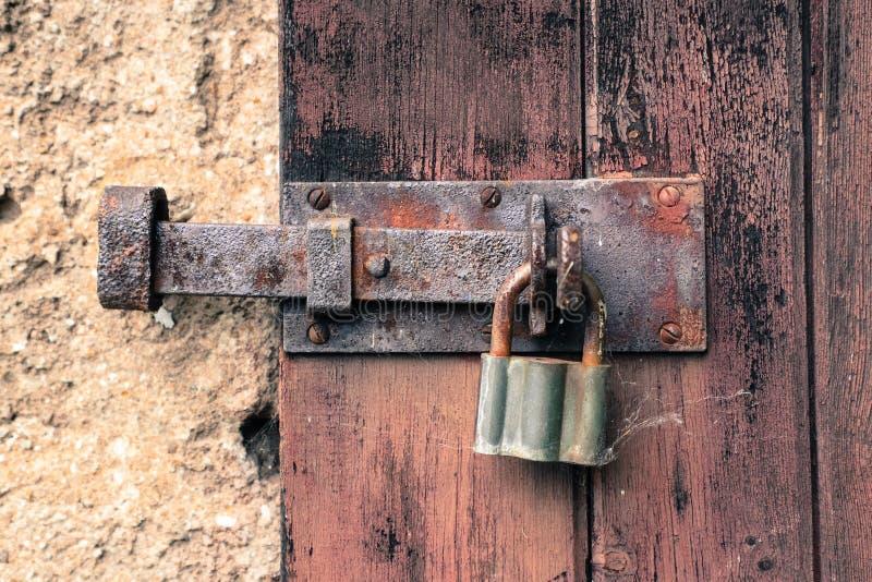 闭合的老生锈的铁锁和葡萄酒在崩裂和剥挂锁被风化的红色木门 免版税库存图片