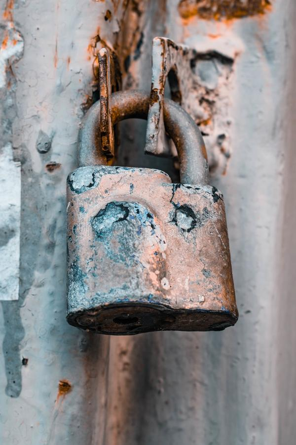 闭合的老生锈的锁 在金属篱芭的背景在难看的东西样式门的 库存照片