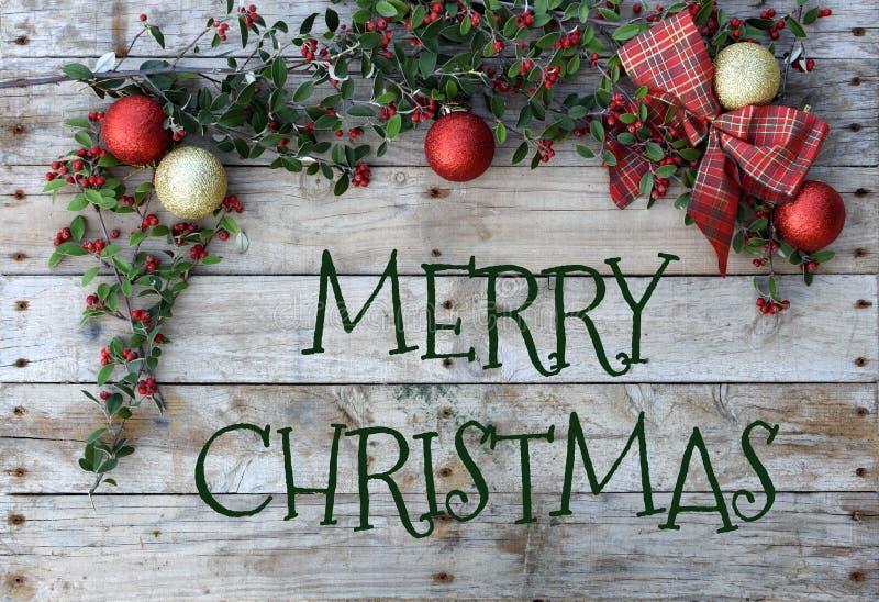 问候的圣诞节明信片 在自然木背景的金属信件 红色,金黄和白色Xmas墙纸 免版税库存照片