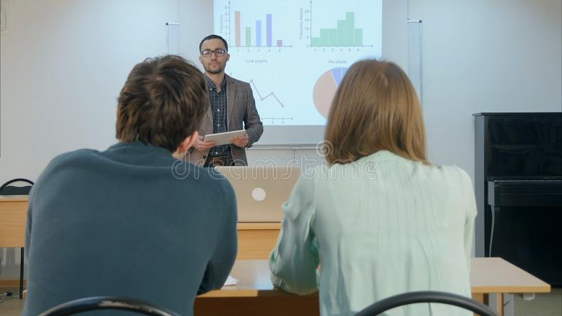 问的男学生举手和老师问题坐桌 免版税库存图片
