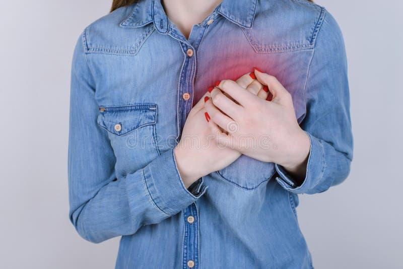 问题的第一种症状心脏概念的 播种紧密握在胸口的哀伤的不快乐的生气夫人照片手被隔绝  库存照片
