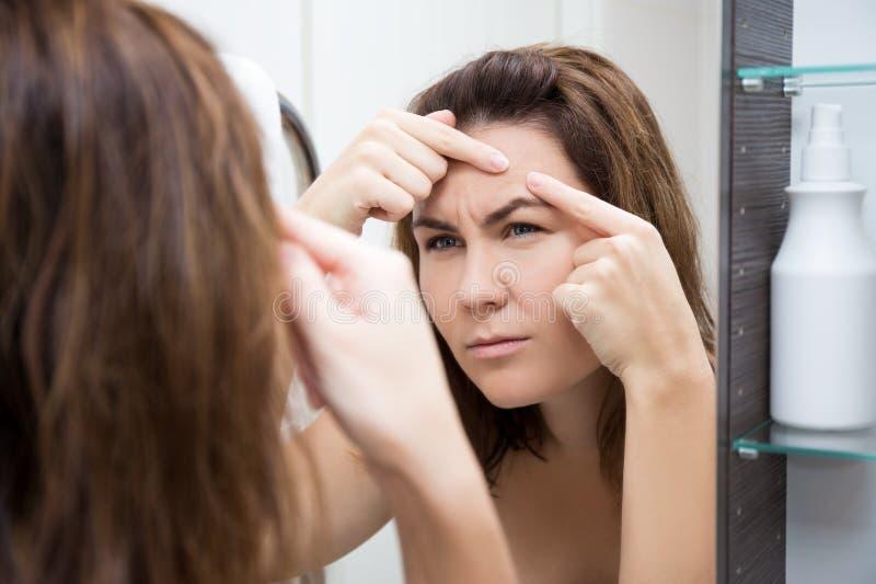 问题皮肤概念-看镜子的哀伤的妇女 免版税库存照片