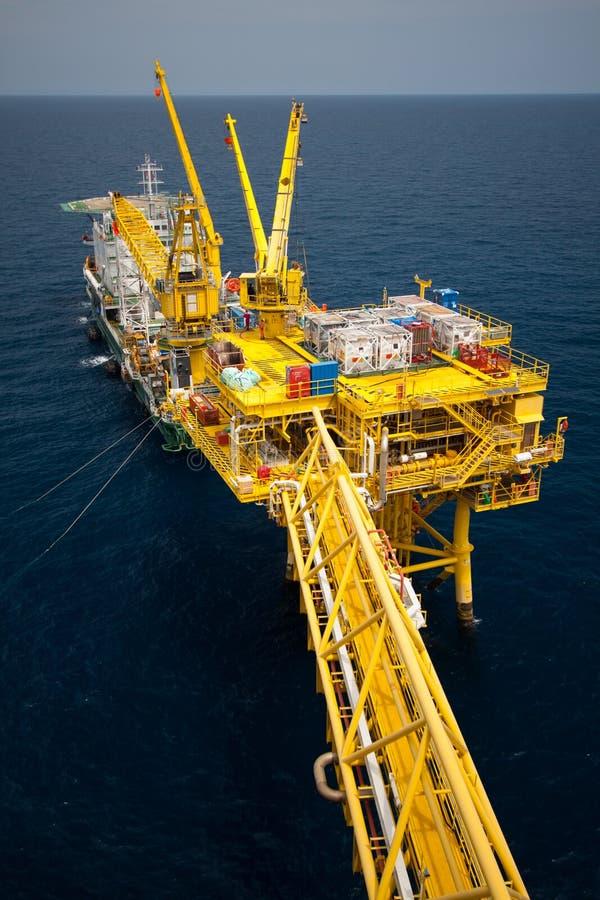 闯入在近海的设施平台油和煤气产业,供应小船或驳船工作的支持工作者在近海平台 库存照片