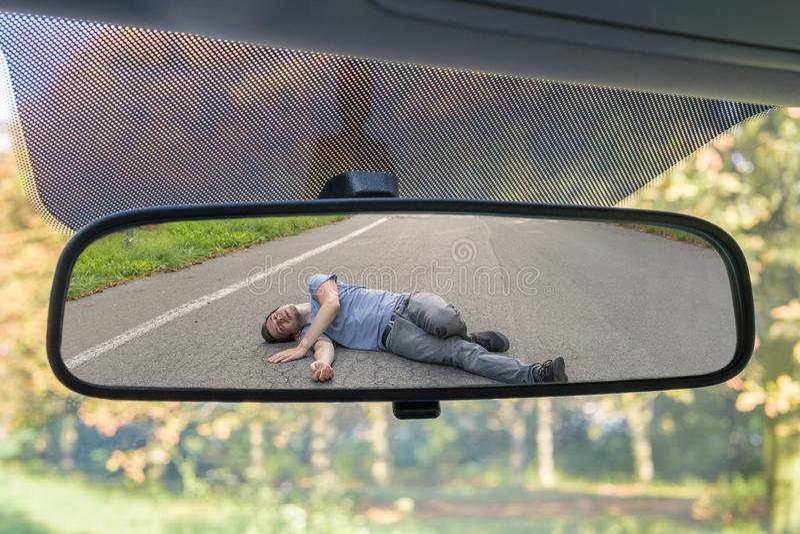 闯祸后逃走的概念 在受伤的人的看法在汽车的后方镜子的路的 库存照片