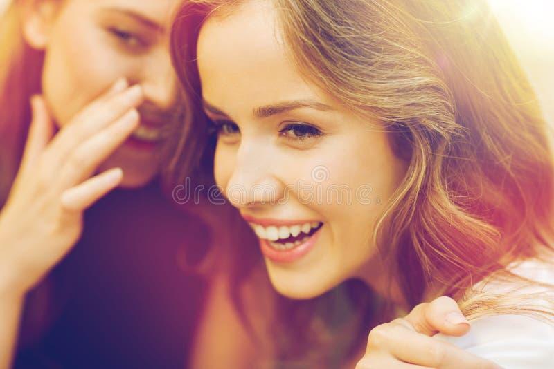 说闲话微笑的少妇和耳语 免版税库存照片