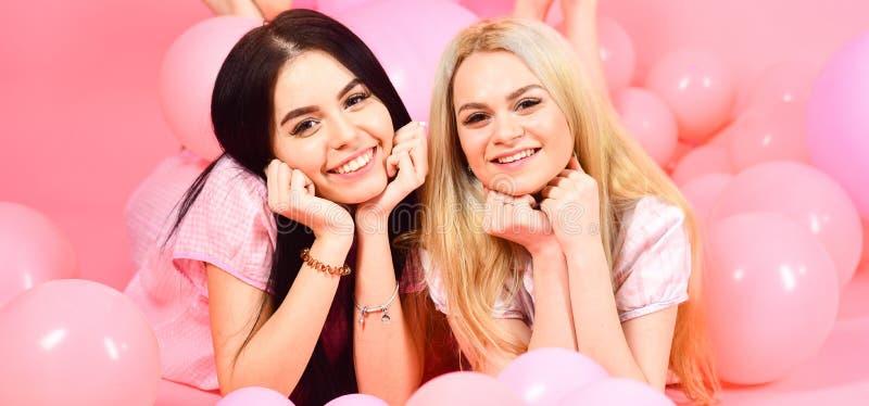 闲话概念 白肤金发和深色在微笑的面孔获得乐趣在国内卧室党 姐妹或最好的朋友  免版税库存图片