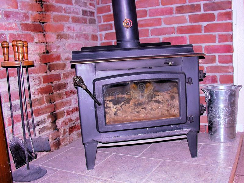 闷燃的生铁木火炉挽救能量 免版税库存照片