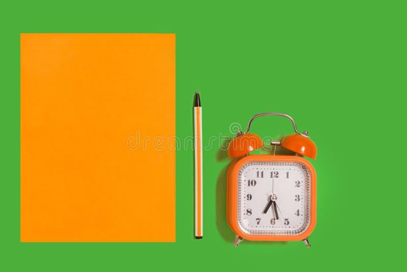 闹钟、纸和笔 免版税库存图片