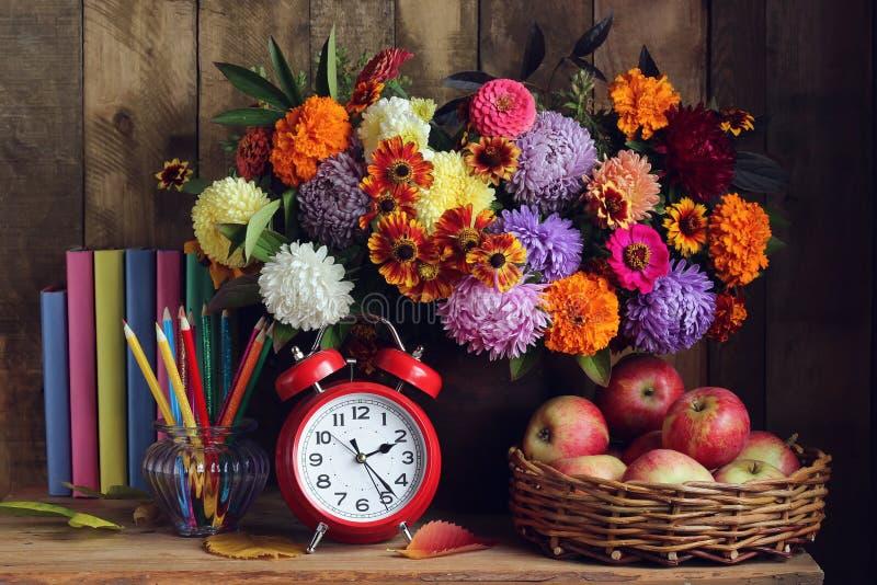 闹钟、花束、苹果在篮子和书在桌上 r 库存图片