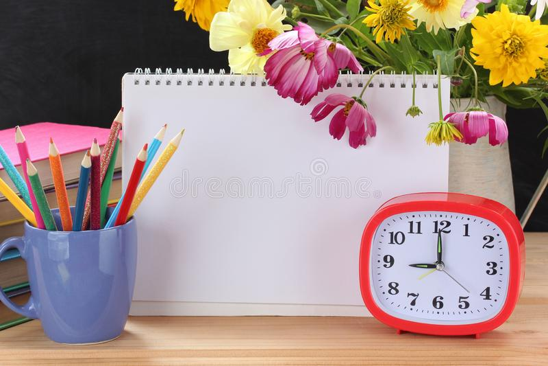 闹钟、花束、课本和开放册页 您的文本的空白页 天9月1日,知识,回到学校 库存图片