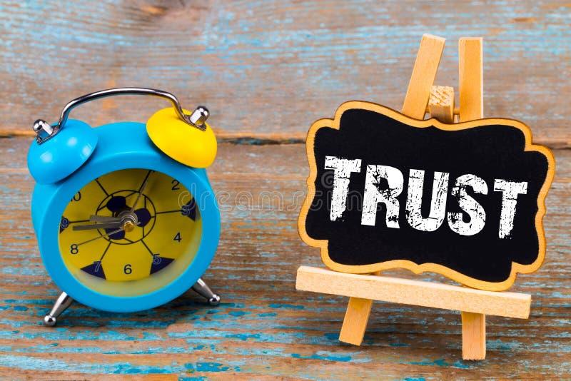 闹钟和一个黑板有文本的-信任,在木后面 免版税库存照片