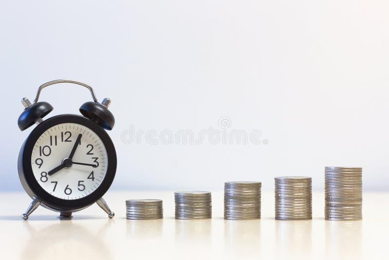闹钟和堆硬币 赢利和事务的概念 免版税图库摄影