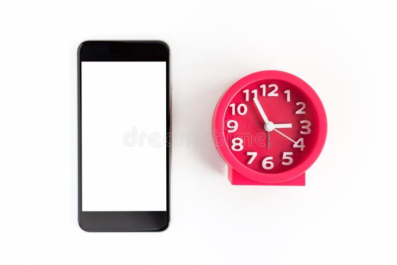 闹钟和巧妙的电话在白色背景 库存图片